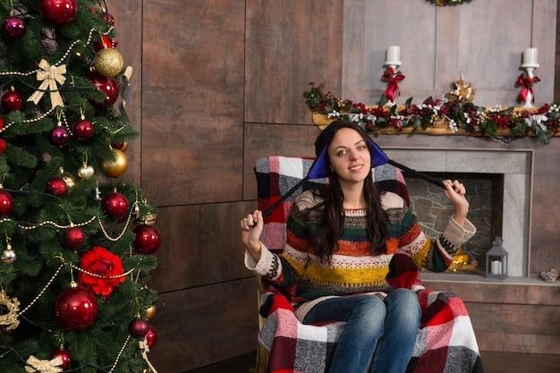 装飾された暖炉のあるリビングルームのクリスマスツリーの近くのロッキングチェアに座っている面白いニット北欧の帽子の魅力的な笑顔の女性
