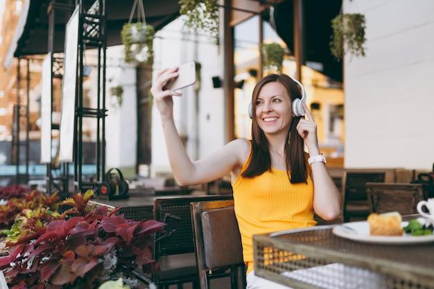 テーブルに座って、ヘッドフォンで音楽を聴いたり、携帯電話で自分撮りショットをしたり、レストランの自由時間でリラックスした