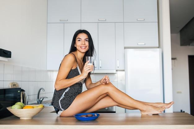 Привлекательная улыбающаяся женщина в пижаме завтракает на кухне утром, ест печенье и пьет молоко, здоровый образ жизни, длинные худые ноги