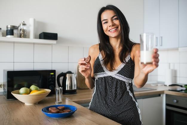 잠옷에 매력적인 웃는 여자, 아침에 부엌에서 아침 식사, 비스킷을 먹고 우유를 마시고, 건강한 라이프 스타일