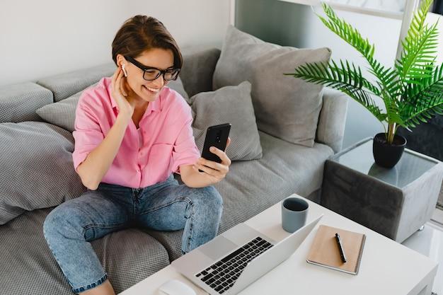 Привлекательная улыбающаяся женщина в розовой рубашке расслабленно сидит на диване у себя дома за столом, работая онлайн на ноутбуке из дома