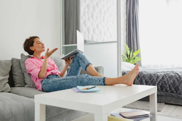 분홍색 셔츠를 입은 매력적인 웃는 여성이 집에서 노트북으로 온라인 작업을 하는 테이블에서 집 소파에 편안하게 앉아 있다