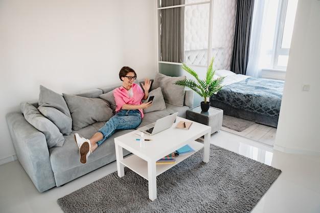 Привлекательная улыбающаяся женщина в розовой рубашке расслабленно сидит на диване у себя дома в современной внутренней комнате за столом, работая онлайн на домашнем ноутбуке