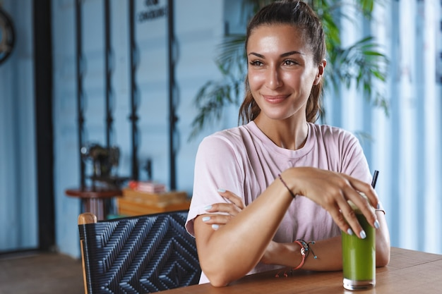휴가에 매력적인 웃는 여자, 파라다이스 리조트를 즐기고, 휴대 전화를 사용하고 건강한 스무디를 마시는 카페에 앉아있다.
