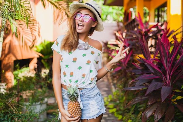 印刷されたtシャツ麦わら帽子夏のファッション、パイナップルを持って手で休暇中の魅力的な笑顔