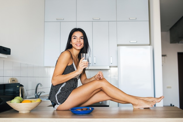 Attractive smiling woman in pajamas having breakfast in kitchen in morning, eating biscuits and drinking milk, healthy lifestyle, long skinny legs