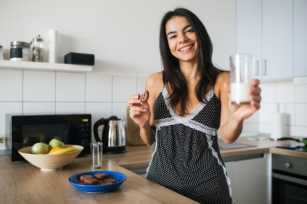Attractive smiling woman in pajamas having breakfast in kitchen in morning, eating biscuits and drinking milk, healthy lifestyle