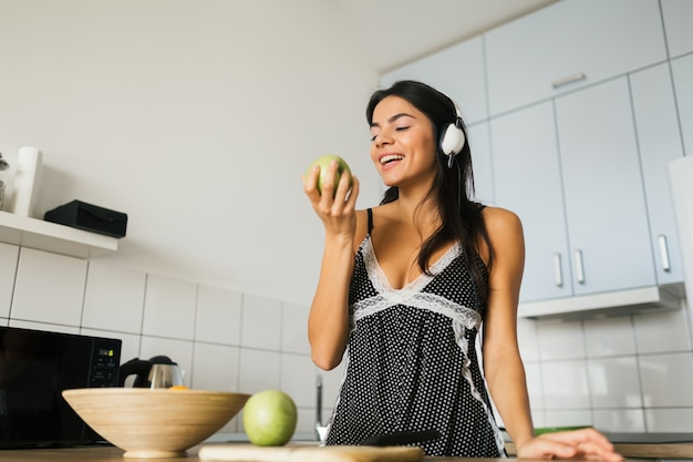 Attractive smiling woman in pajamas having breakfast in kitchen in morning, healthy lifestyle, eating apple, listening to music on headphones