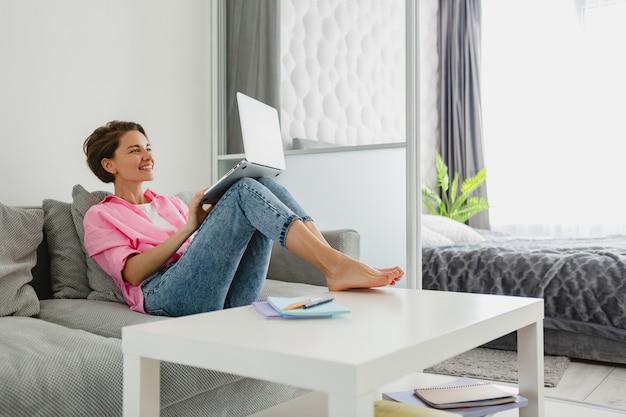 Attraente donna sorridente in camicia rosa seduta rilassata sul divano di casa a tavola che lavora online sul laptop da casa