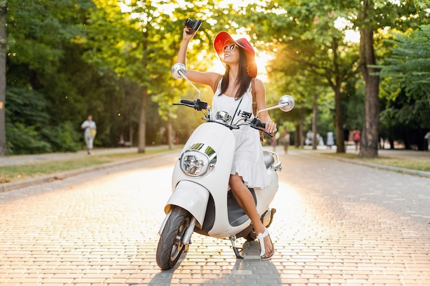 Attractive smiling woman riding on motorbike in street in summer style outfit wearing white dress and red hat traveling on vacation, taking pictures on vintage photo camera