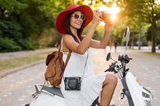 Привлекательная улыбающаяся женщина, едущая на мотоцикле по улице в летнем стиле, в белом платье и красной шляпе, путешествующая в отпуске, фотографируя на старинный фотоаппарат