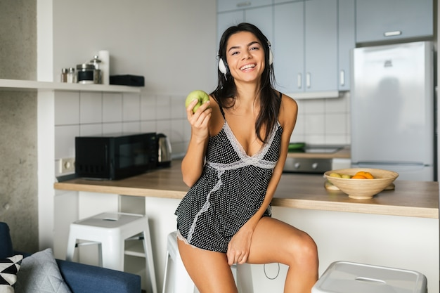 Attractive smiling woman in sexy pajamas having breakfast in kitchen in morning, healthy lifestyle, eating apple, listening to music on headphones