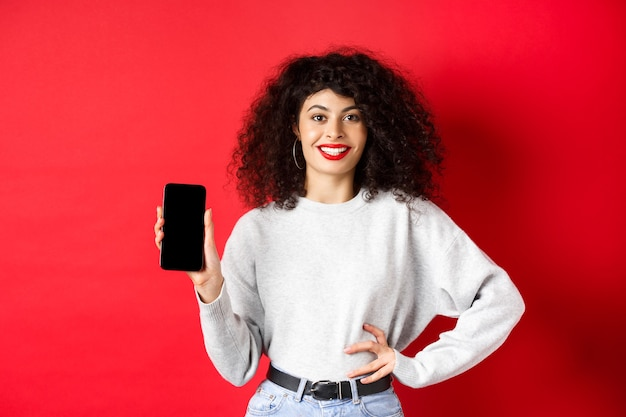 Attractive smiling woman showing empty smartphone screen and looking happy, advertising online store or application, standing against red background.