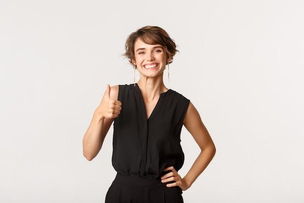 Привлекательная улыбается женщина показывает палец вверх в утверждении, рекомендуя продукт, стоя белый.