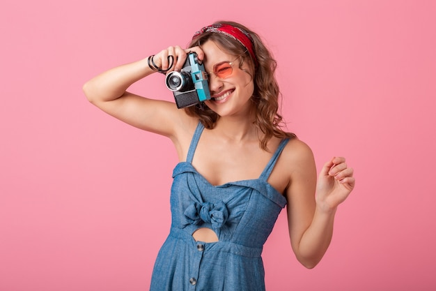 Attractive smiling woman taking photo on vintage camera, pointing finger up, wearing denim dress and sunglasses isolated on pink background