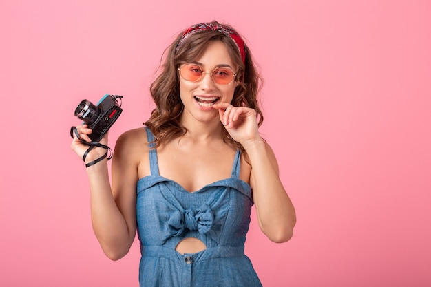 Attractive smiling woman taking photo on vintage camera wearing denim dress and sunglasses isolated on pink background, flirty funny face expression