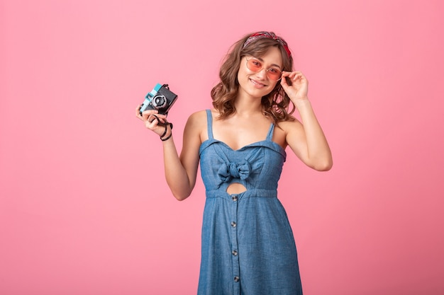 Attractive smiling woman taking photo on vintage camera wearing denim dress and sunglasses isolated on pink background