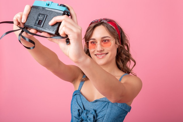 Attractive smiling woman taking self portrait photo on vintage camera wearing denim dress and sunglasses isolated on pink background