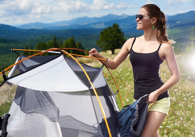 Attractive smiling woman tourist hiking mountain trail, standing near tent, holding backpack, enjoying summer sunny morning in mountains. camping lifestyle adventure outdoor concept