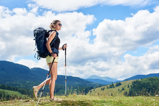 Attractive smiling woman tourist hiking mountain trail, walking on grassy hill, wearing backpack, using trekking sticks, enjoying summer sunny day in the mountains. tourism concept