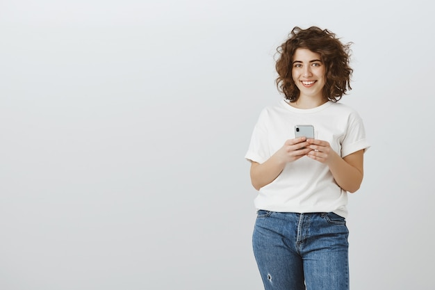 휴대 전화, 문자 메시지, 스크롤 소셜 미디어를 사용하여 매력적인 웃는 여자