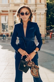 Attractive smiling woman walking on sunny weather in autumn city wearing sexy blue suit