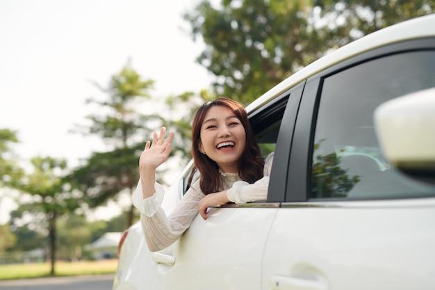 車の窓から手を振っている魅力的な笑顔の女性。