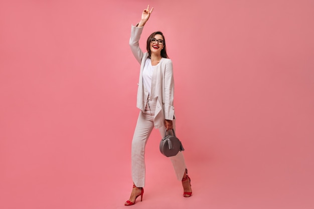 Attractive smiling woman in white modern suit and eyeglasses holds handbag and shows peace sign on pink isolated background.