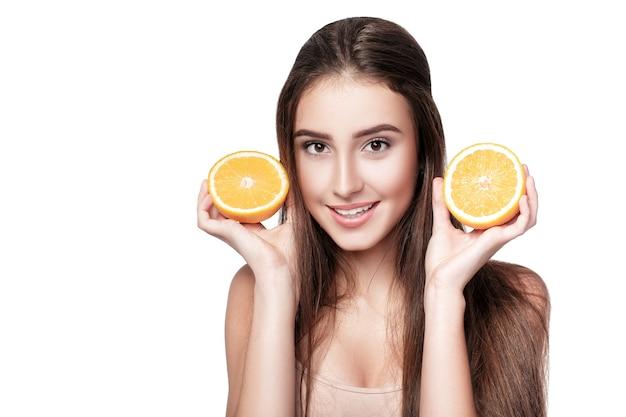 白い背景で隔離のオレンジと魅力的な笑顔の女性。健康食品