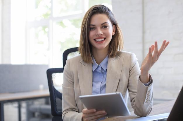 Привлекательная улыбающаяся женщина, работающая на планшете в современном офисе.
