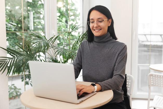 Привлекательная улыбающаяся женщина, работающая на ноутбуке в кафе