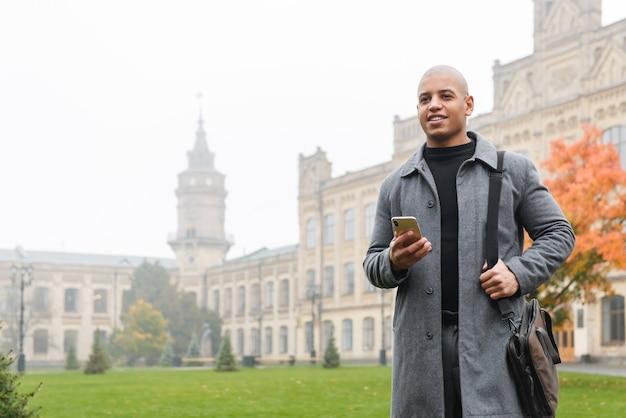 Привлекательный улыбающийся молодой африканский мужчина в осеннем пальто гуляет на улице города, используя мобильный телефон