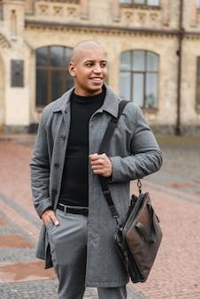 Привлекательный улыбающийся молодой африканец в осеннем пальто гуляет на улице по городской улице