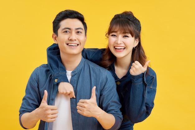 黄色のスタジオの背景に孤立して幸せで驚いている魅力的な笑顔の若いアジアのカップル