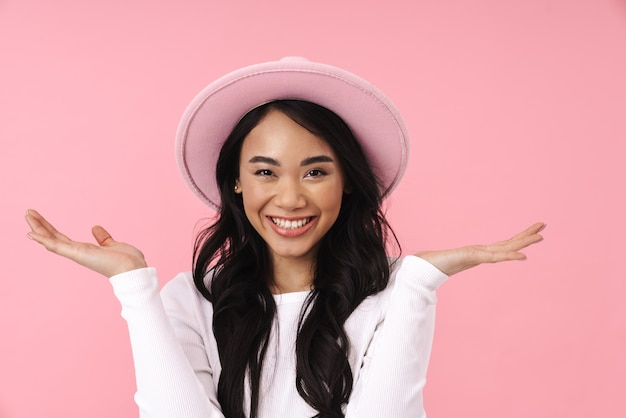 Attractive smiling young asian woman wearing casual clothes standing isolated over pink wall, posing in hat