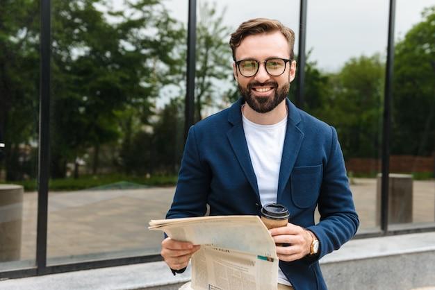 Привлекательный улыбающийся молодой бородатый мужчина в куртке читает газету, стоя на улице в городе и пьет кофе на вынос