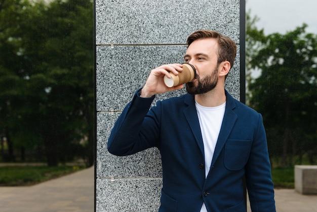 Привлекательный улыбающийся молодой бородатый мужчина в куртке стоит на открытом воздухе в городе и пьет кофе на вынос