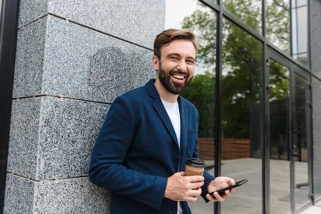 수염을 기른 매력적인 젊은이가 재킷을 입고 도시에 야외에 서서 테이크아웃 커피를 마시는 동안 휴대폰을 사용하여 재킷을 입고 있습니다.