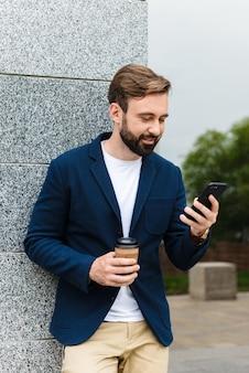 Привлекательный улыбающийся молодой бородатый мужчина в куртке с помощью мобильного телефона, стоя на улице в городе и попивая кофе на вынос