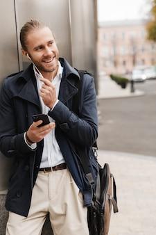 Привлекательный улыбающийся молодой светловолосый мужчина в формальной одежде разговаривает через наушники, держа мобильный телефон, стоя на улице на улице города