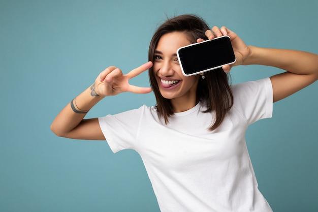 Привлекательная улыбающаяся молодая брюнетка женщина хорошо выглядит в белой футболке, стоящей изолированной на синем