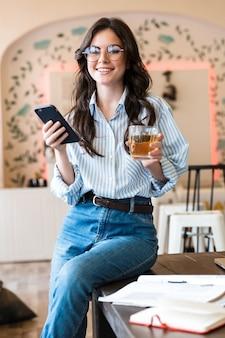 Привлекательная улыбающаяся молодая брюнетка женщина учится в кафе в помещении, используя мобильный телефон, держа стакан с соком