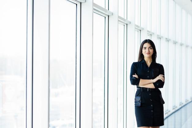 Привлекательная улыбающаяся молодая бизнес-леди. портрет счастливой жизнерадостной молодой леди со скрещенными руками на стене окна бизнес-центра.