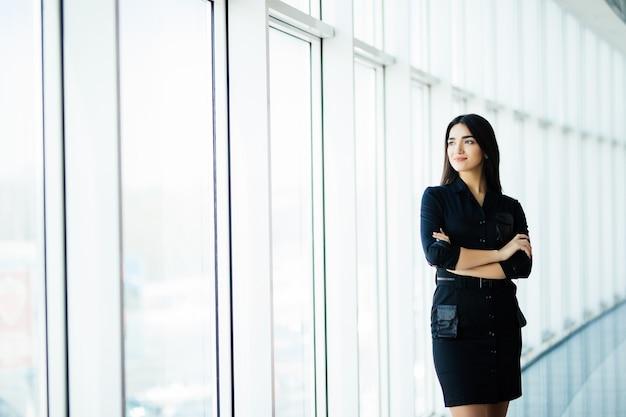 매력적인 웃는 젊은 비즈니스 우먼. 비즈니스 센터 창 벽에 두 팔을 교차 행복 쾌활 한 젊은 아가씨의 초상화.