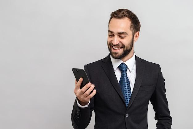 Привлекательный улыбающийся молодой бизнесмен в костюме, стоящий изолированно над серой стеной, держа мобильный телефон