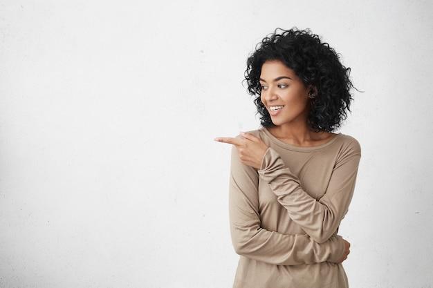 Attraente giovane cliente femminile sorridente con capelli ricci che guarda lateralmente