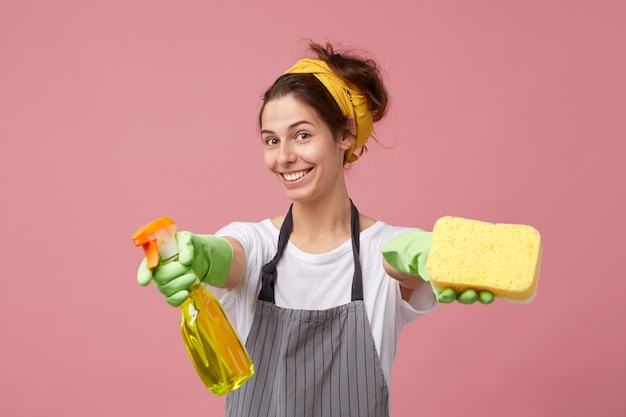 Attractive smiling young female dressed in casual clothes and protective wear outstretching her arms with cleaning spray and sponge as if saying: would you like to help me with housework?