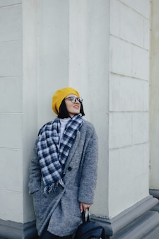 Attractive smiling young girl in glasses in coat and yellow beret on a simple light background