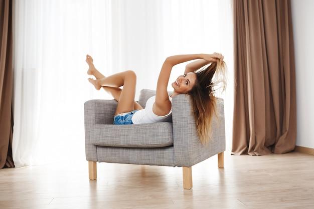 Привлекательная улыбающаяся молодая девушка лежит на кресле и позирует