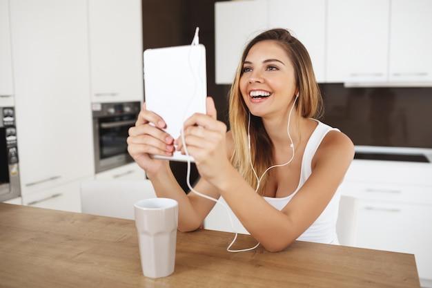 Ragazza sorridente attraente che si siede alla compressa della tenuta della tavola di cena e che parla con gli amici tramite messaggero